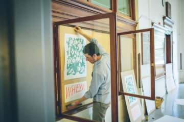Scott installing his prints at the Old Post Office