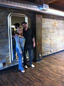 Debbie Pitzer and Tom at Bryson Speer Salon (Federal Way, WA) in front of a 25 foot wall finish that she created using a hybridized plaster mix and a special tool she created to apply over concrete blocks. She used a metallic rust finish on the two supports to make them look like iron beams.