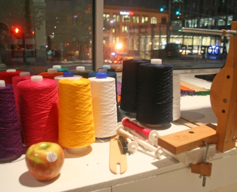 Colorful cotton threads were transformed into wearable garments, some were given out to those in need, and some were sold to passersby with the profit being donated to a nearby shelter.