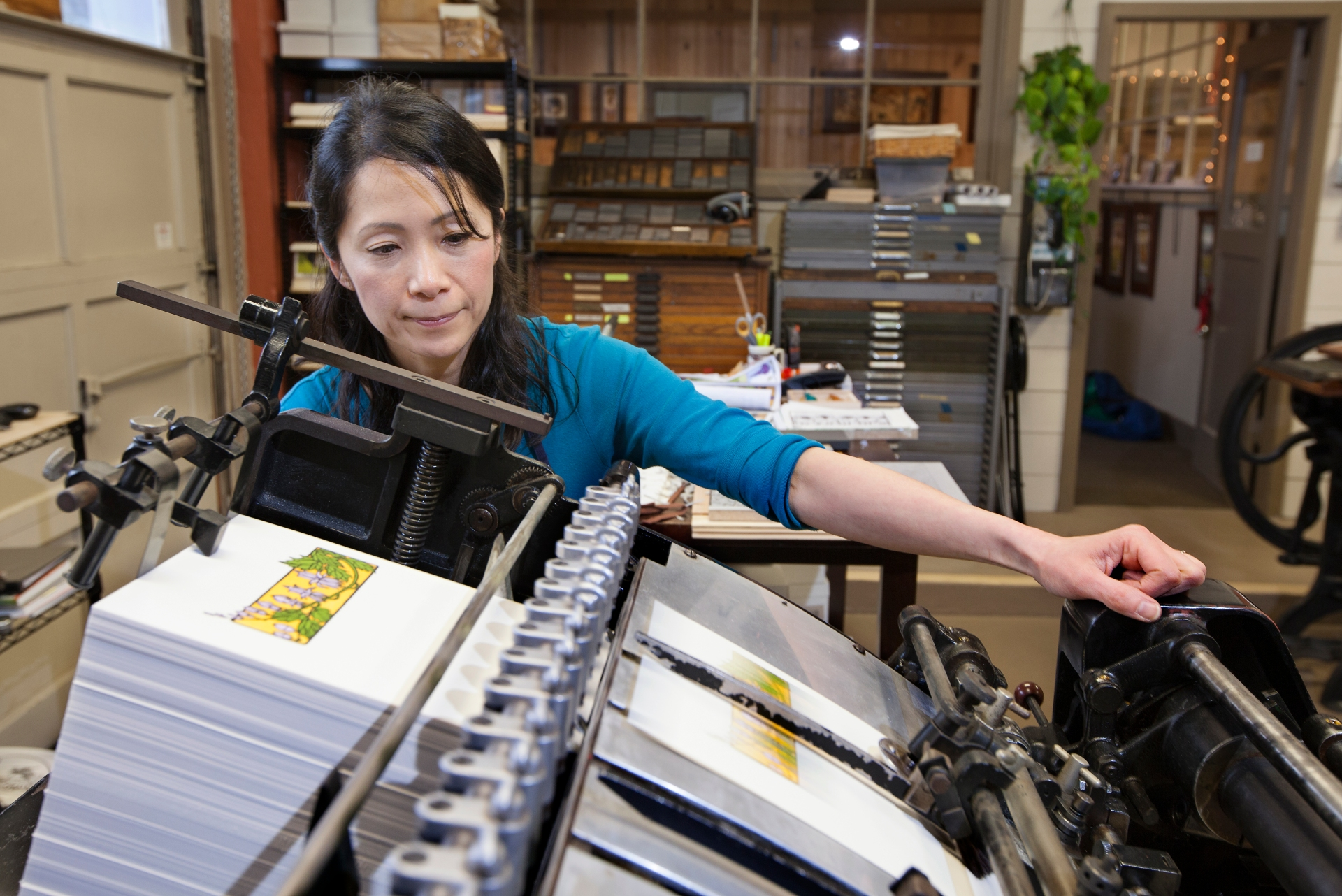 Tacoma letterpress artist Yoshiko Yamamoto checks registration quality on a set of note cards. The Arts & Crafts Press combines Japanese woodblock style with Western letterpress techniques.