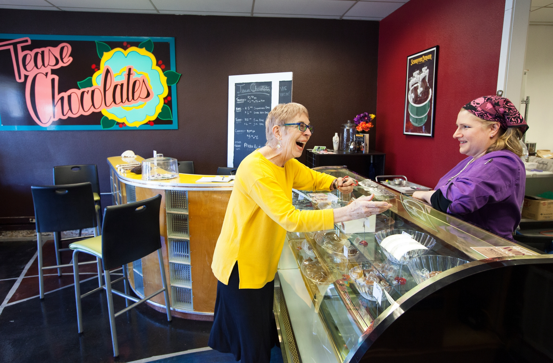 Tease Chocolates co-owner Julie Farrell shares a laugh with a customer in her shop.