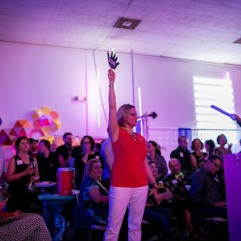 Tacoma Arts Administrator Amy McBride raises paddle high during live auction at NEON 2016. Photo by Scott Haydon.