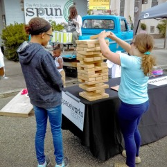 Spaceworks hosted an information booth with games and prizes next to SPUN at the Hilltop Street Fair in 2016. The giant jenga was a smash hit with kids and adults alike. Photo courtesy of Spaceworks.