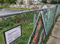 Advertisemounts: This detail of the fence on 6th Ave and Ainsworth shows the work that Artscapes participants Tim & April Norris put in to beautify this construction site. Photo by Spaceworks.