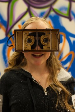 1120 Creative House ArtWalk participant experiences DIY virtual reality goggles made using laser cut plywood at FabLab in Tacoma. Photo by Kris Crews.